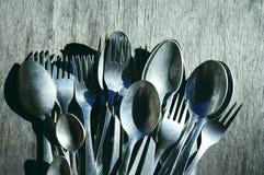 Colheres e forquilhas de alumínio velhas em uma superfície de madeira Imagem de Stock