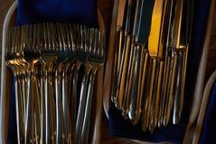 Colheres e forquilhas douradas das facas na bandeja de madeira na tabela Imagem de Stock Royalty Free