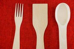 Colheres, forquilha e esp?tula de madeira em um fundo vermelho Vista de acima imagens de stock royalty free