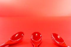 Colheres plásticas vermelhas no fundo vermelho Fotografia de Stock