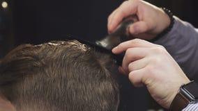 Colhido perto acima de um cabelo do corte do barbeiro de seu cliente com um ajustador filme