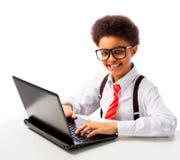 Écolier d'afro-américain avec l'ordinateur portable Photographie stock libre de droits