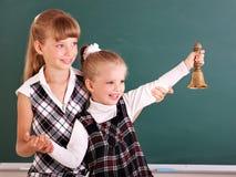 Écoliers dans la salle de classe près du tableau noir. Image stock