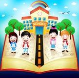 Écoliers sur le livre rouge avec le bâtiment scolaire et l'arc-en-ciel Photographie stock