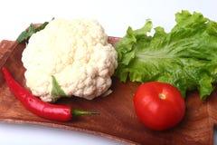 Coliflor fresca, tomate, hojas de la ensalada y otras verduras en el tablero de madera Aliste para cocinar Comida vegetariana Imágenes de archivo libres de regalías