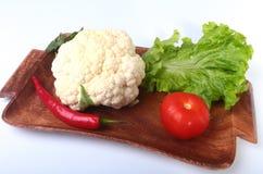 Coliflor fresca, tomate, hojas de la ensalada y otras verduras en el tablero de madera Aliste para cocinar Comida vegetariana Foto de archivo