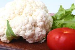 Coliflor fresca, tomate, hojas de la ensalada y otras verduras en el tablero de madera Aliste para cocinar Comida vegetariana Imagen de archivo