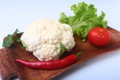 Coliflor fresca, tomate, hojas de la ensalada y otras verduras en el tablero de madera Aliste para cocinar Comida vegetariana Imagen de archivo libre de regalías