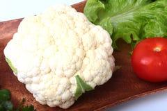 Coliflor fresca, tomate, hojas de la ensalada y otras verduras en el tablero de madera Aliste para cocinar Comida vegetariana Imagenes de archivo