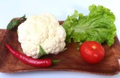 Coliflor fresca, tomate, hojas de la ensalada y otras verduras en el tablero de madera Aliste para cocinar Comida vegetariana Fotos de archivo libres de regalías