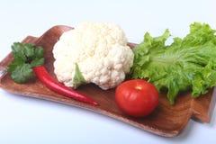 Coliflor fresca, tomate, hojas de la ensalada y otras verduras en el tablero de madera Aliste para cocinar Comida vegetariana Fotografía de archivo