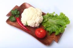 Coliflor fresca, tomate, hojas de la ensalada y otras verduras en el tablero de madera Aliste para cocinar Comida vegetariana Fotografía de archivo libre de regalías