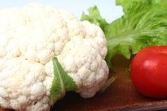 Coliflor fresca, tomate, hojas de la ensalada y otras verduras en el tablero de madera Aliste para cocinar Comida vegetariana Fotos de archivo