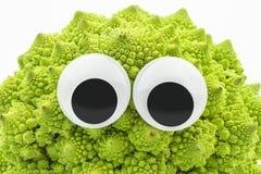 Coliflor verde con los ojos googly en el fondo blanco foto de archivo