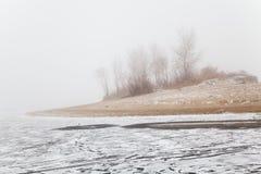 Colina en la niebla en una playa congelada invierno del río Imágenes de archivo libres de regalías