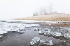 Colina en niebla en una playa congelada invierno del río Fotografía de archivo libre de regalías