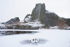 Colina rocosa volcánica cubierta por la nieve durante la puesta del sol nublada del invierno Fotos de archivo