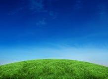 Colina verde bajo el cielo azul Imágenes de archivo libres de regalías