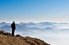 Colinas de la montaña y silueta brumosas del hombre Fotografía de archivo