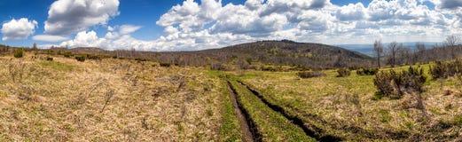 Colinas del panorama de la primavera con un camino de tierra Imagenes de archivo