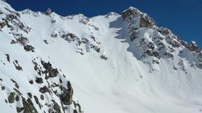 Colinas rocosas escarpadas de una montaña con las porciones de la nieve fresca del polvo, cantidad aérea en 4k almacen de metraje de vídeo