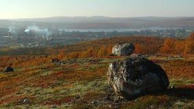 Colinas septentrionales rojas brillantes del otoño con las rocas y la ciudad más allá metrajes