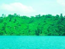 Colinas verdes cerca del lago azul con el cielo hermoso Fotos de archivo