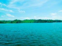 Colinas verdes cerca del lago azul con el cielo hermoso Foto de archivo