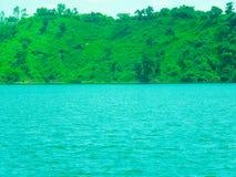 Colinas verdes cerca del lago azul con el cielo hermoso Imagen de archivo