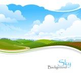 Colinas verdes, cielo azul y camino solo Imagenes de archivo