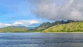 Colinas verdes con el centro tropical de la vegetación del océano Fotos de archivo