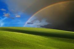 Colinas verdes y fondo del arco iris Fotos de archivo libres de regalías