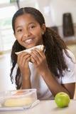 Écolière appréciant son déjeuner dans le cafétéria d'école Images stock
