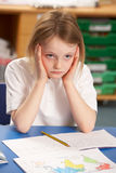 Écolière chargée étudiant dans la salle de classe Photos stock