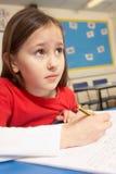 Écolière chargée étudiant dans la salle de classe Images stock