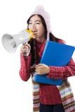 Écolière dans l'usage d'hiver criant avec le mégaphone Image libre de droits