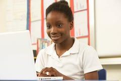Écolière dans LUI classe utilisant l'ordinateur Photos libres de droits
