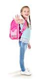 Écolière de sourire avec le sac à dos disant au revoir Photos stock