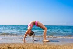 Écolière effectuant la gymnastique sur le bord de la mer Image libre de droits