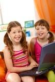 Écolières heureuses avec l'ordinateur portatif Photographie stock libre de droits