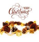 Colisões e presentes dourados no fundo branco com Feliz Natal do texto Rotulação da caligrafia Fotos de Stock Royalty Free