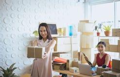 Colis asiatique heureux de participation de propriétaire de femme d'affaires et travail ensemble, début de sourire femelle vers l photos stock