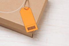 Colis attaché avec de la ficelle avec le label orange d'adresse joint photographie stock