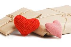 Colis avec le papier d'emballage et les coeurs rouges d'isolement sur le blanc Photos stock