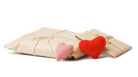 Colis avec le papier d'emballage et les coeurs rouges d'isolement sur le blanc Image stock