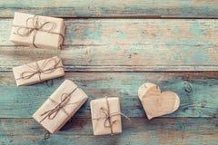 Colis de cadeau et coeur en bois découpé sur un fond de vieux verrat Images libres de droits