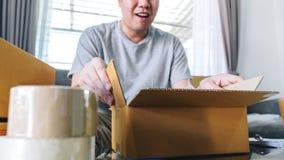 Colis de petite entreprise pour embarquer, boîte en ligne de paquet d'achats d'ouverture heureuse d'homme avec le colis tout en s photo libre de droits