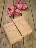 Colis enveloppés dans le papier brun et la ficelle avec le decorat rouge de contrôle photographie stock