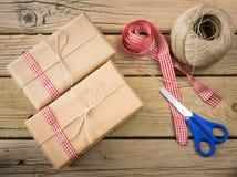 Colis enveloppés dans le papier brun et la ficelle avec le ruban et le scisso Image stock