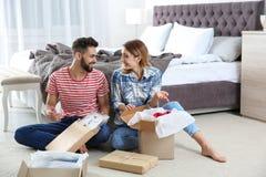 Colis s'ouvrants de jeunes couples dans la chambre à coucher photo stock